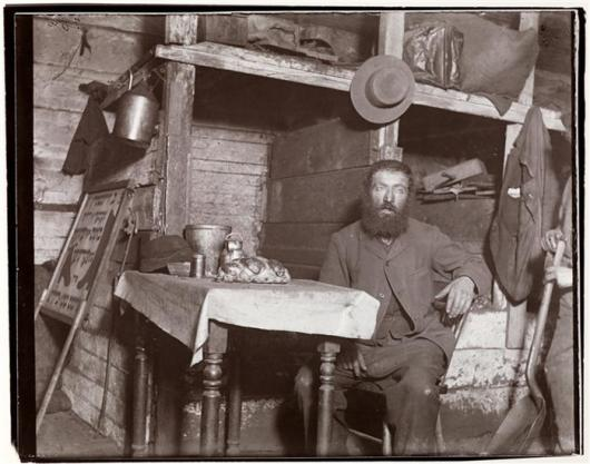 Ludlow Street: Hebrew making ready for Sabbath Eve in his coal cellar -- bread on his table